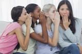 Friends whispering secret to shocked brunette
